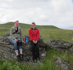 two woman sitting on a rock