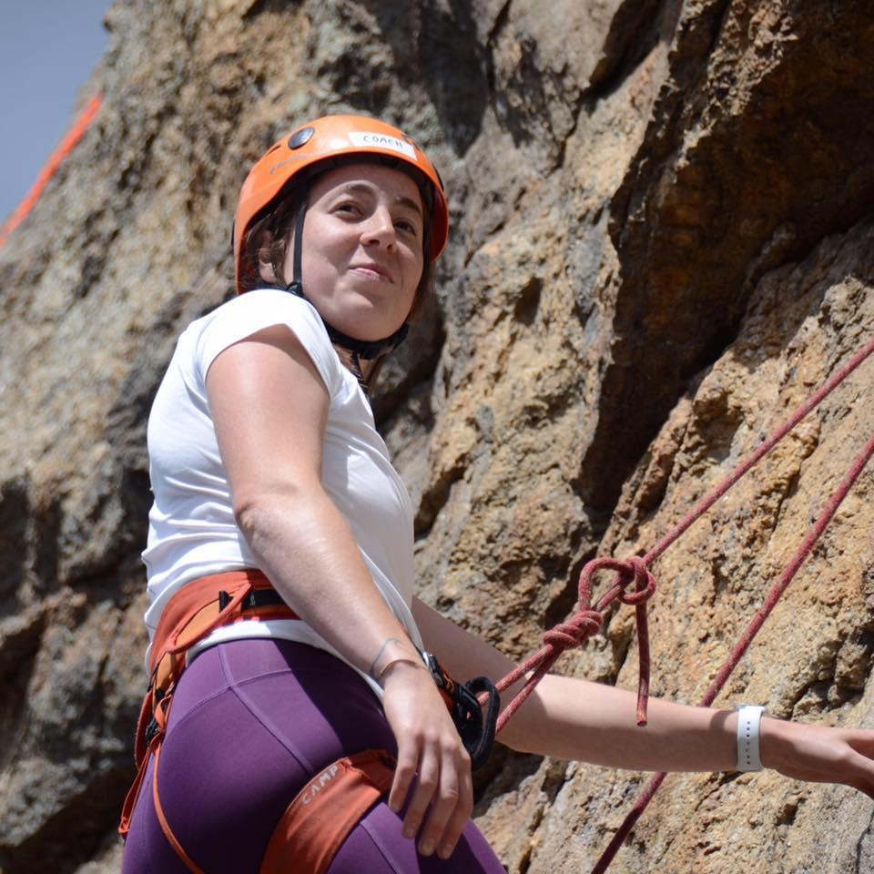 Hannah P. climbing a cliff