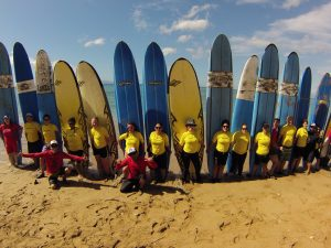 Group of campers with surf boards behind them